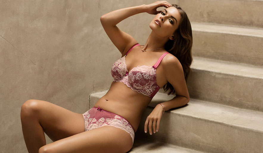 Woman wearing matching Marianna Raspberry bra and briefs, sitting on steps